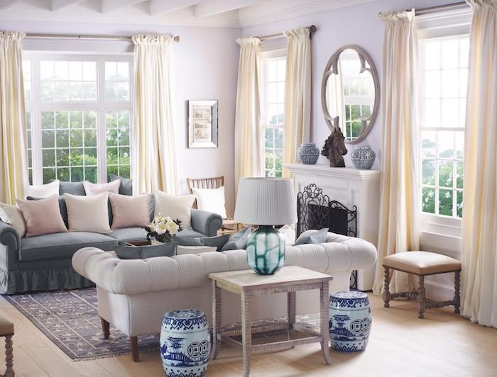exmeple de peinture interieur maison lavande clair, rideaux ecru, canapé gris clair et gris foncé, parquet bois clair, miroir rond, deco traditionnelle somptueuse