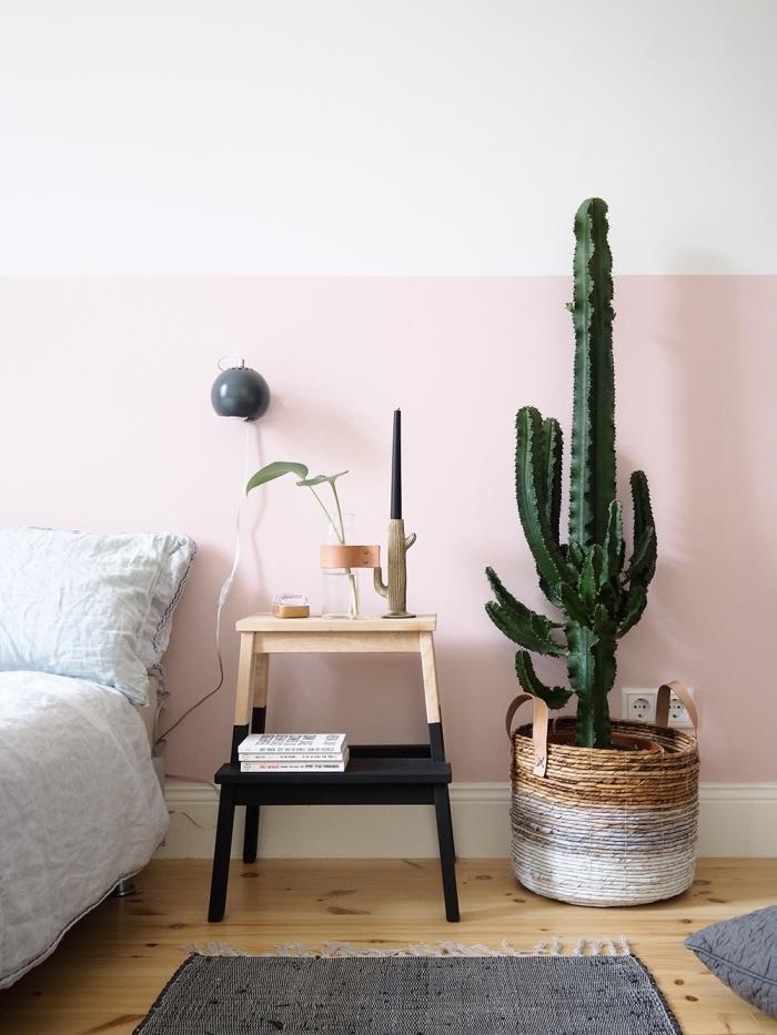 idée déco chambre adulte de style jungalow, pièce aux murs blanc et rose pastel avec parquet bois clair et meuble bois