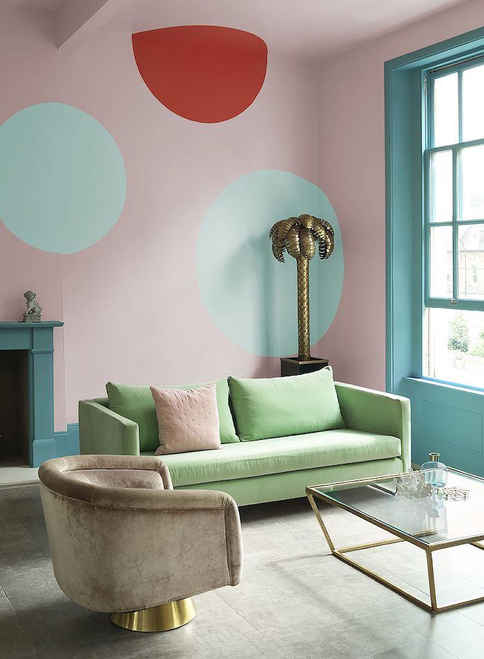 mur couleur rose pastel, nuance rose poudré avec déco de cercles de peinture rouge et vert, canapé vert pistache, fauteuil gris, table basse verre et laiton