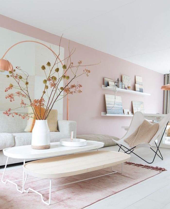 murs couleur rose clair et tapis rose clair sur parquet blanc, tables basses gigognes, chaise pliante blanche, vase rempli de branches d arbre