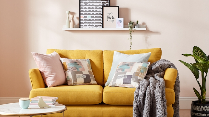 couleur saumon sur les murs et canapé jaune décoré de coussins en tons pastel, plaid gris tricot, table basse marbre