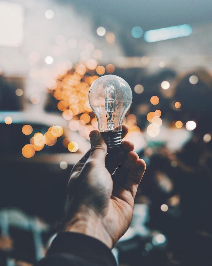Main tenant une bulbe électrique, bokeh effet photographie, idées pour rénover votre maison