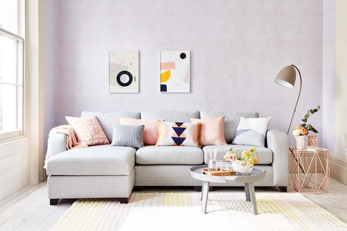murs couleur lilas, nuance lavande clair pour decorer un salon romantique à ambiance féminine, canapé gris, coussins decoratifs colorés, tableaux art geometrique
