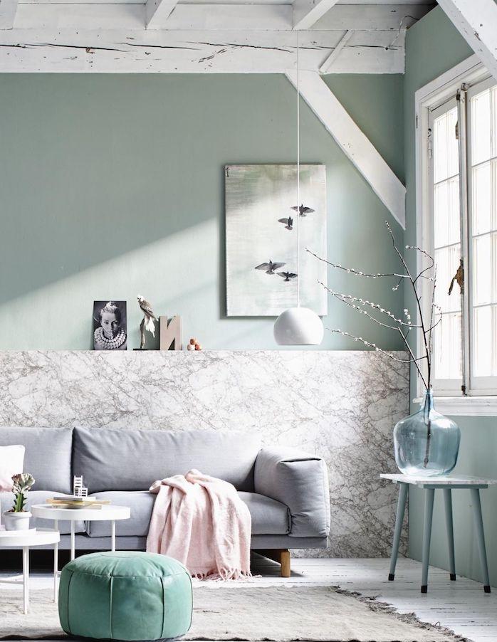 deco scandinave salon aux murs vert de gris et pan de mur effet marbre, tapis gris sur sol aprquet blanc, canapé gris clair, pouf vert d eau