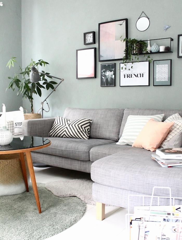 decoration salon moderne gris de vert, canapé gris, table basse bois et verre, deco murale de cadres, tapis gris rond