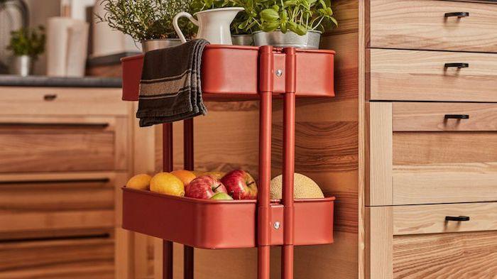 ranger fruits et herbes dans une cuisine sur desserte cuisine ikea de couleur rouge adossée à un ilot central en bois