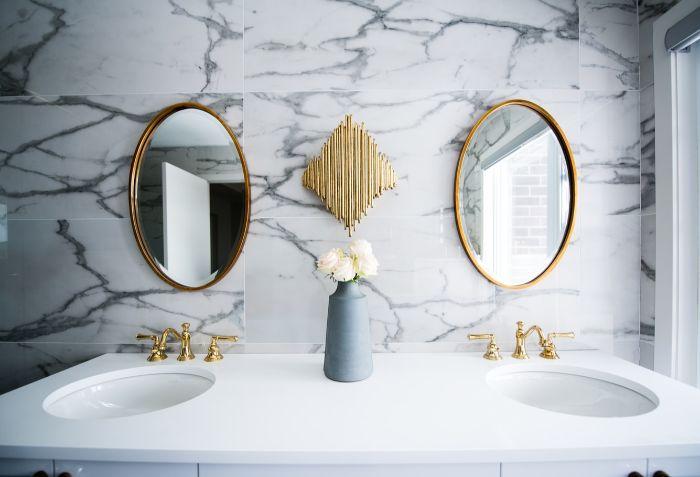 salle de bain en marbre blanc et gris, fleurs blancs dans une salle de bain en marbre, miroirs ovales