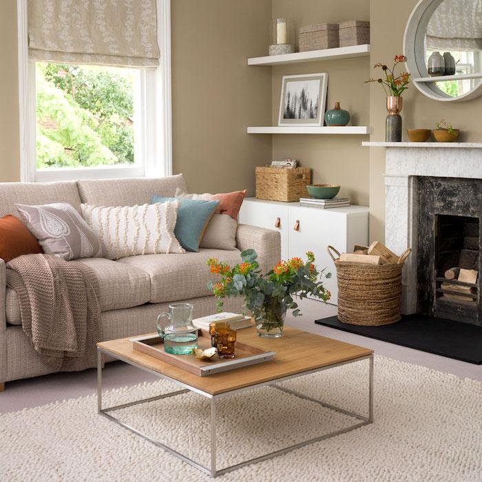 decoration salon moderne gris taupe, cheminée décorative, canapé gris clair, table basse bois et metal, miroir rond blanc, coussins decortifs en couleur