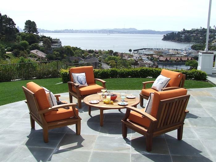 Photo terrasse avec belle vue de la mer, table basse ronde, fauteuils oranges coussins, comment aménager son salon de jardin design