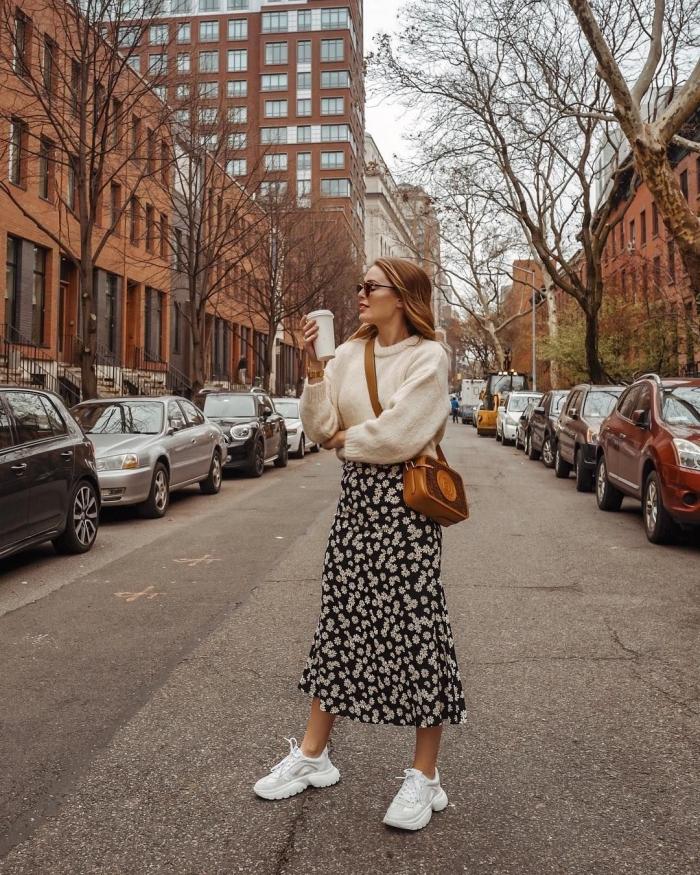 look casual chic femme hiver, tenue en jupe taille haute midi noire à imprimés fleuris blancs avec pull beige et sneakers