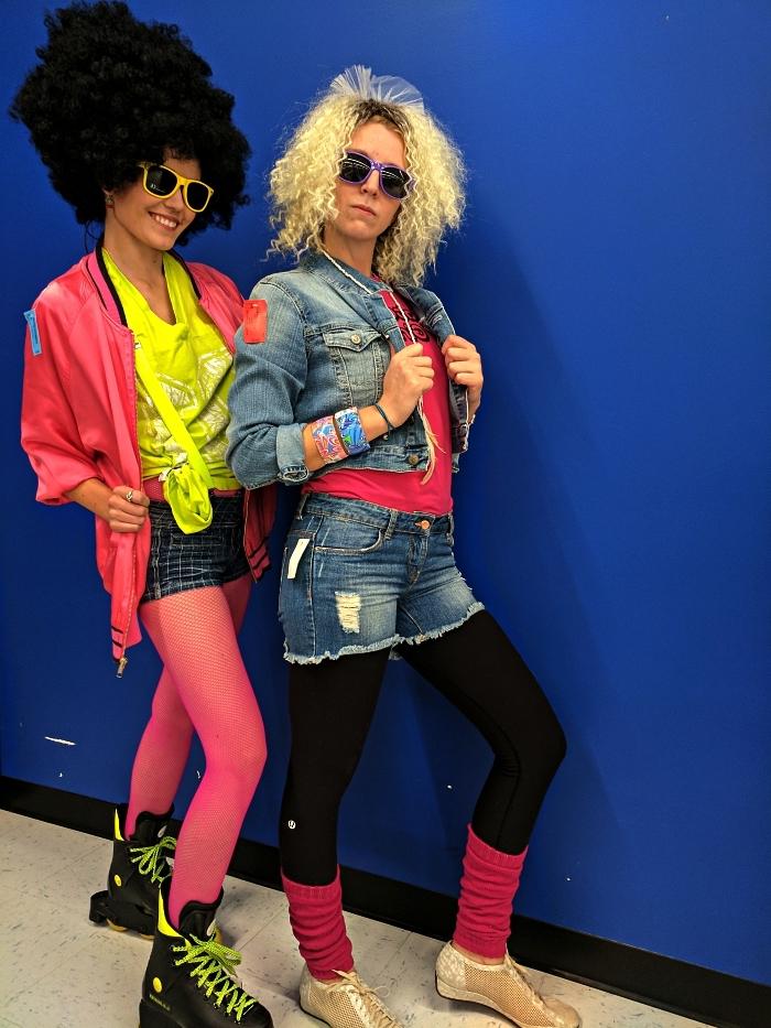 déguisement disco femme des années 80 composé de shorts, collant en résille rose, haut coloré et perruque de coiffure des années 80