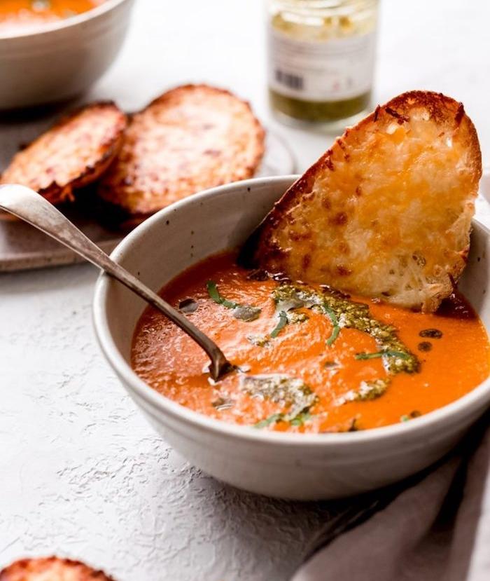 repas du soir léger avec oignons, tomates, carottes, soupe facile garnie de feuilles de basilic et toast aux fromages