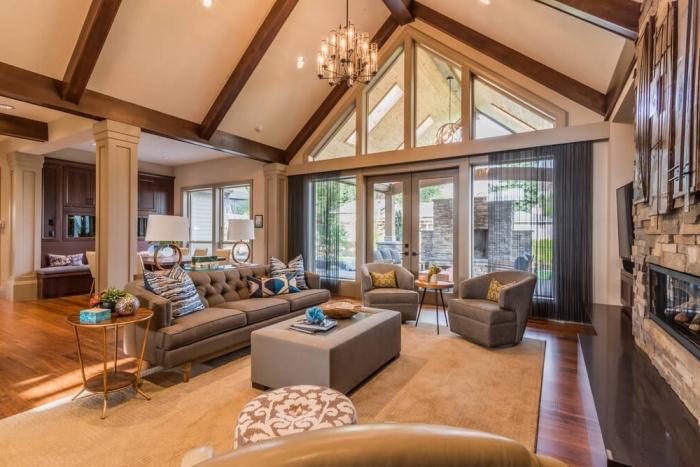 idée décoration intérieure salon élégant en couleurs neutres avec accents bois et cheminée pierre, mobilier salon en tissu gris