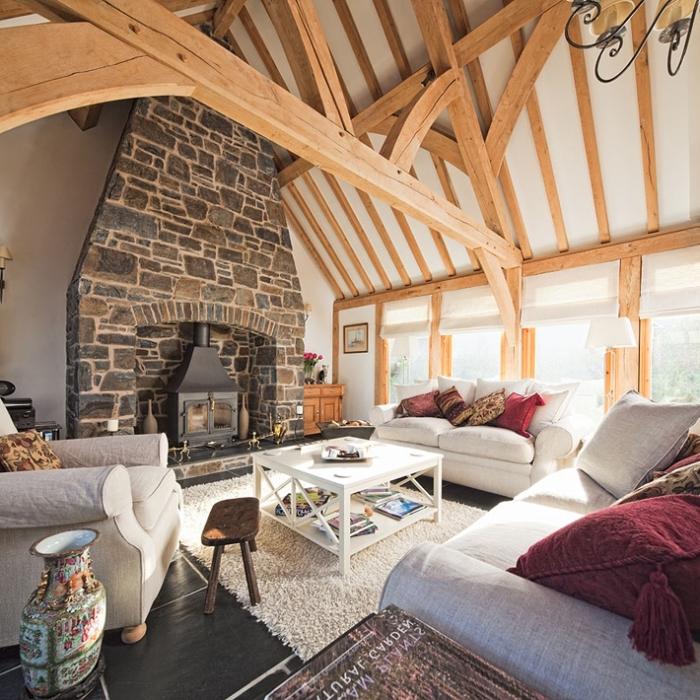 idée design sejour cathédrale de style rustique aux murs blancs avec cheminée en pierre et plafond à poutres bois