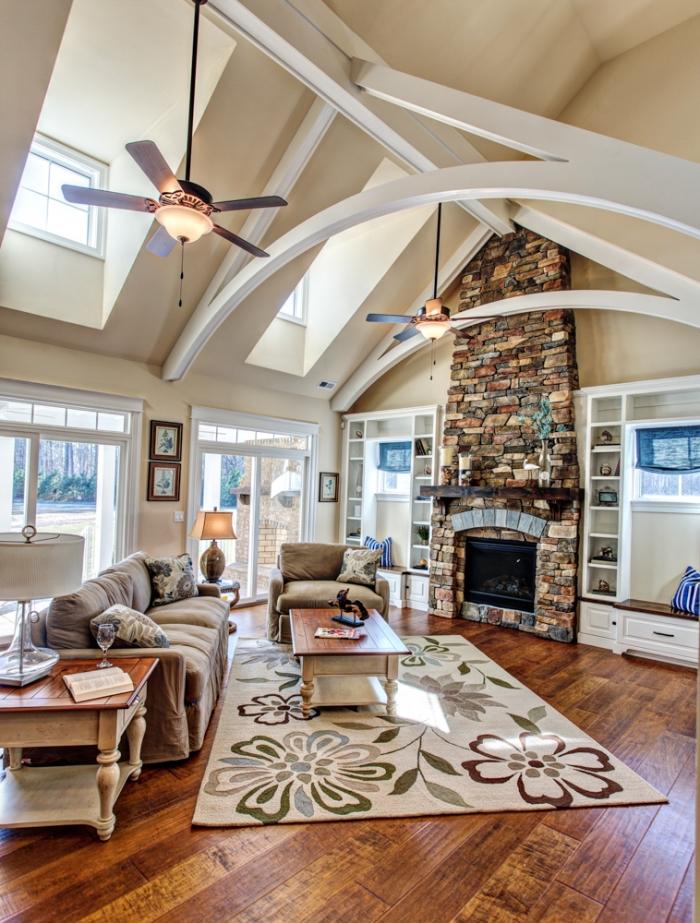 exemple de déco sous plafond cathédrale de style rustique, comment aménager un salon avec parquet bois foncé et cheminée pierre