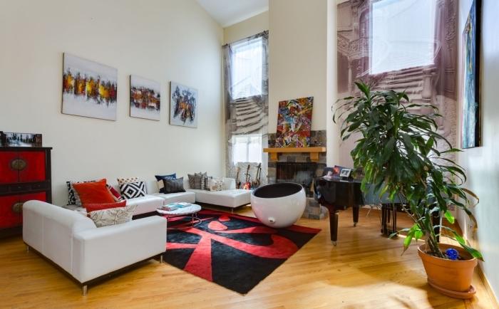 idée salon beige et bois avec accents de couleur rouge, modèle de salon à toit cathédrale avec deux pentes