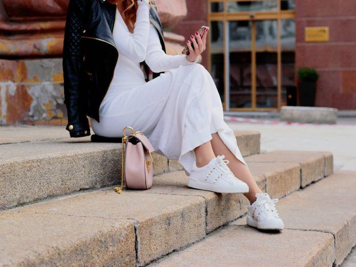 Escalier de batiment publique, femme en robe blanche longue et veste moto en cuir noir, sac à main rose