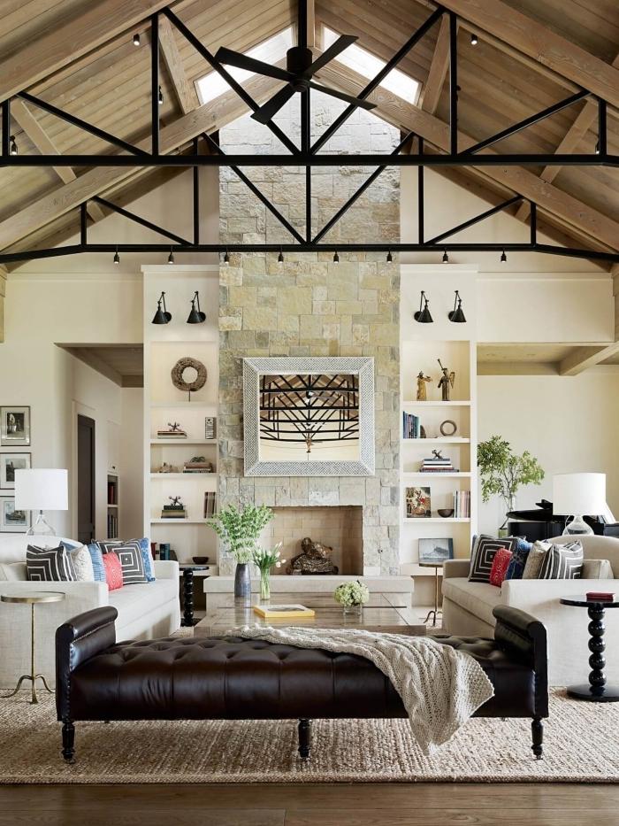 amenagement salon blanc avec plafond à deux pentes couvert de planches bois et fenêtres, idée déco salon cozy avec cheminée