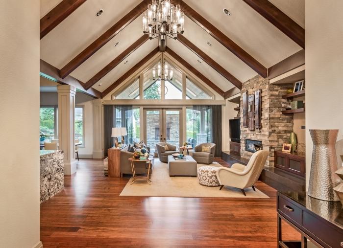 design intérieur stylé dans un salon à plafond blanc avec poutres bois et spots led, modèle toit à deux pentes