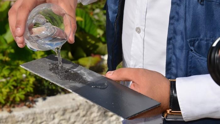 Homme qui montre la différence de la peinture hydrofuge, rénover votre maison en pensant pour la protection de l'humidité