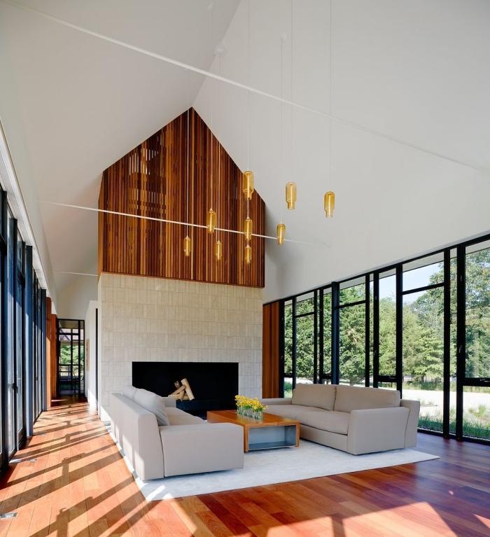design intérieur stylé dans un salon à plafond haut avec grandes fenêtres, idée deco salon cosy en blanc et bois avec accents noirs