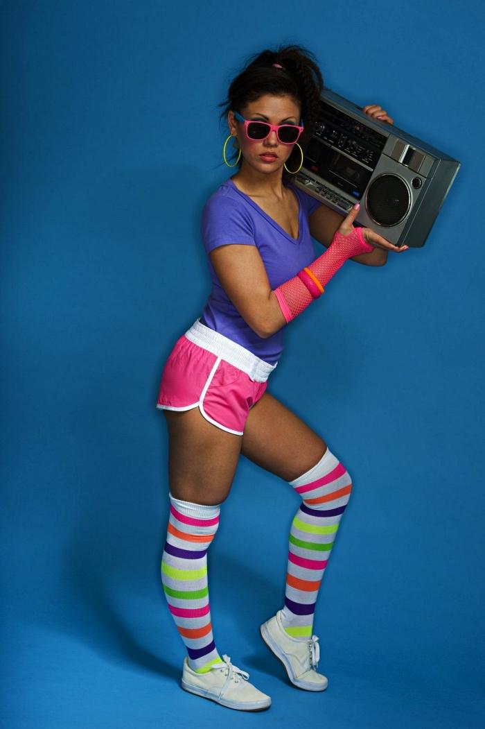 tenue de sport de femme des années 80 comosé de t-shirt violet, short de sport rétro et chaussettes hautes à rayures multicolores