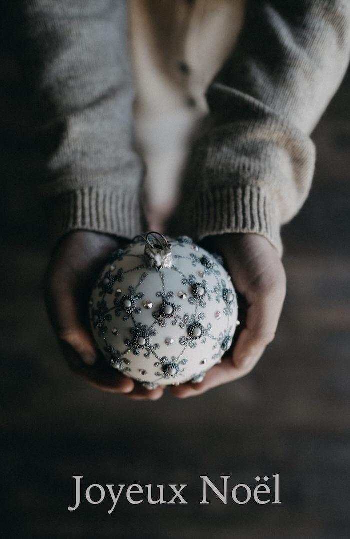 Blanche boule de noel avec décorations, pull beige, mains image joyeux noël, envoyer une carte de voeux