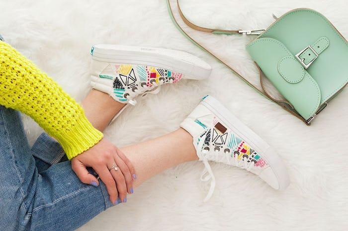 Basket blanche personnalisé à l'aide de broderie coloré, savoir comment customiser ses chaussures, femme assise sur le sol portant jean slim et pull jaune