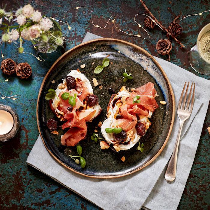 Assiette noire sur serviette en lin blanche, table industrielle bleu joliment décoré, aperitif noel, que mettre sur une bruschetta assaisonné d'huile d'olive et vinegre, prosciutto et mozzarelle