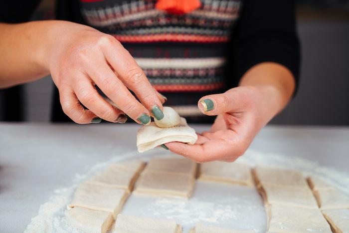 envelopper une boule de mozzarella dans un carré de pâte pour faire un apéritif original de noel