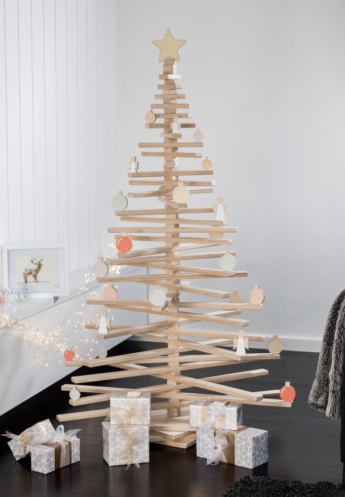 diy sapin de noel en bois fabriqué avec planches de bois clair sur des morceaux en bois comme support tronc de sapin
