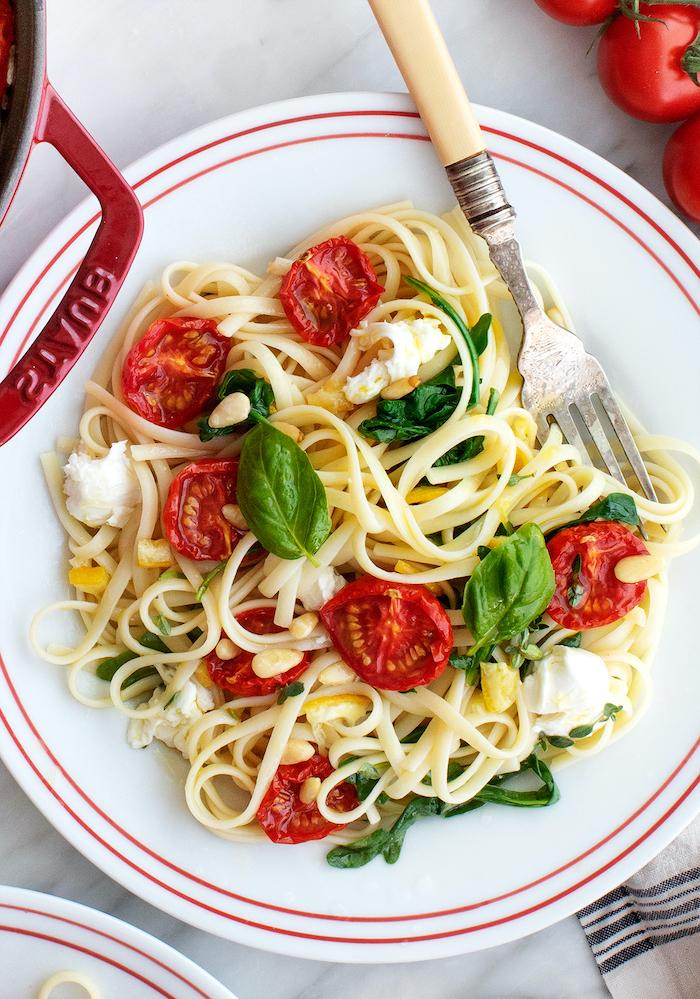 assiette remplie de spaghetti pates aux tomates cerise avec di basilic frais, tomates roties au four, mozzarella et jus de citron