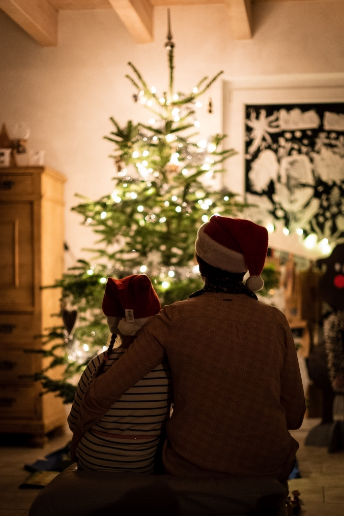 image de joyeux noel avec enfant et son père devant un sapin naturel dans le salon, idée photo noel en famille
