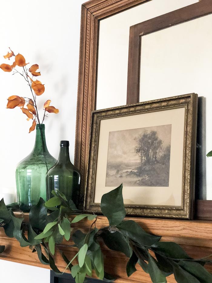 Verte vase dame jeanne, composition florale à faire soi meme, vase en verre avec fleurs oranges dedans et une branche feuilles vertes pour décorer l'espace au-dessus de la cheminée