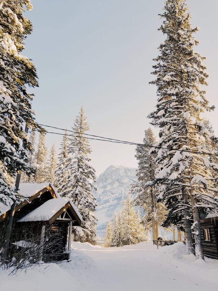 wallpaper iphone pour Noël avec un paysage nature enneigée dans un village au coeur des montagnes avec petites maisons en bois