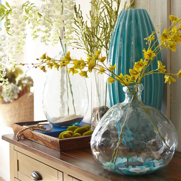 Printemps avec branches fleuries dans les vases diy, bonbonne en verre, intérieur design, superbe déco salon
