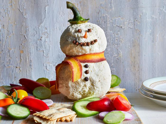 entree simple et bluffante pour votre apero dinatoire de noel, bonhomme de neige en fromages chèvre et fromage à la crème entouré de crackers et legumes