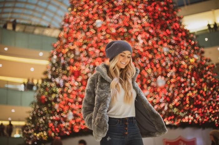 photo joyeux noel avec une fille habillée en jeans et manteau faux fur dans un centre commercial décoré avec géant sapin