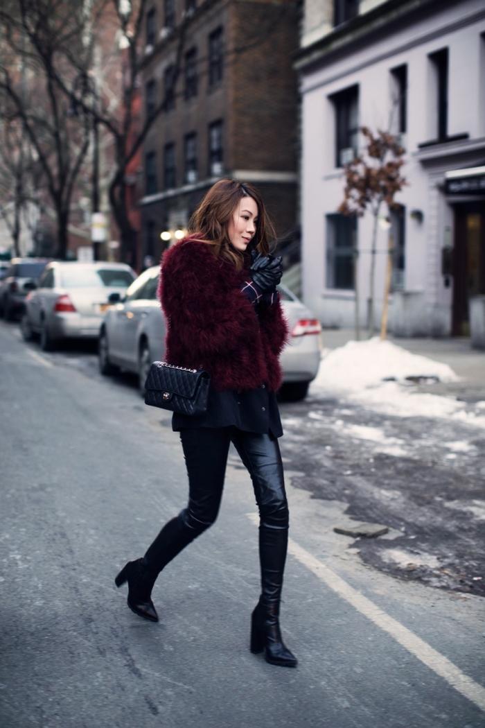 look femme moderne en pantalon fit simili cuir noir porté avec manteau oversize de couleur rouge foncé et accessoires noirs
