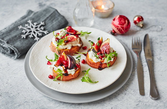 Serviette gris, flacon de neige décoratif, boules de noel rouges, bougie et assiette avec amuse bouche apéritif facile, préparer un toast spécial pour la fête de noël
