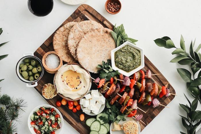 repas a partager entre amis, udee de brochette apero de légumes grillées sur plateau servi avec houmous, fromage feta, olives, pain naan