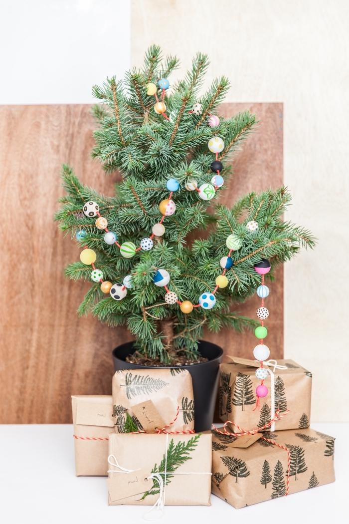 activité manuelle noel facile, idée comment décorer un petit arbre de Noël avec ornements diy en forme de guirlande en perles de bois