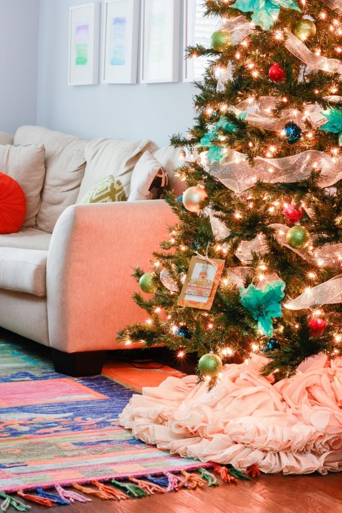 ambiance cozy dans un salon aux murs blancs avec parquet bois foncé, idée deco sapin noel avec boules en bleu et vert