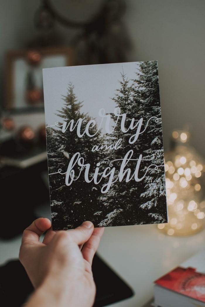photo d'une carte de noel avec image de paysage enneigé et lettres joyeux fêtes devant une deco sapin blanc mini sur bureau blanc