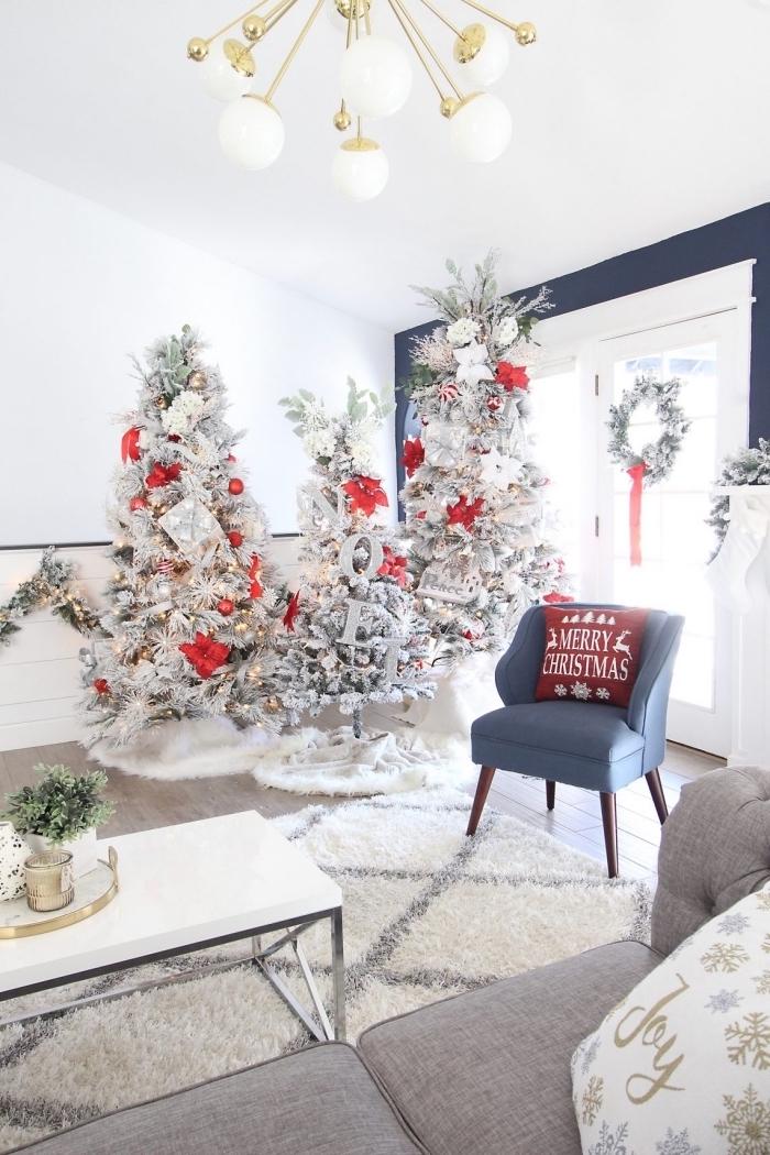 modèles de sapin rouge et blanc dans une pièce sous pente aux murs blancs et sol bois avec meubles en gris