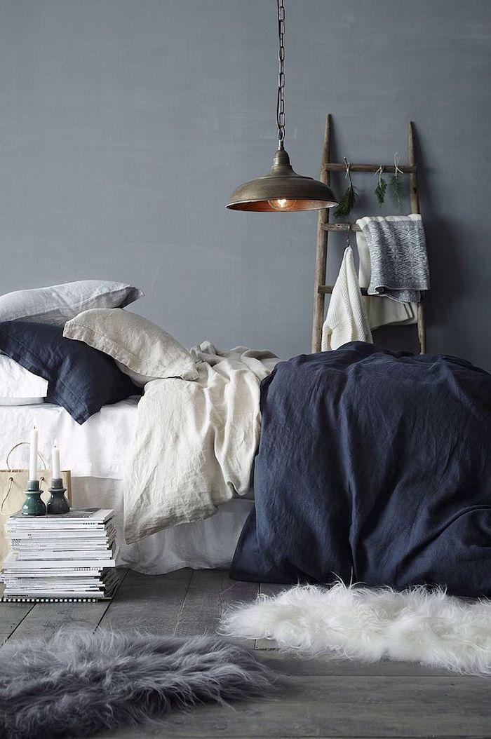 Echelle de rangement, lit avec couverture coton bleu et blanc, coussins sur le lit double confortable, peinture gris clair, est-ce que le gris est une couleur