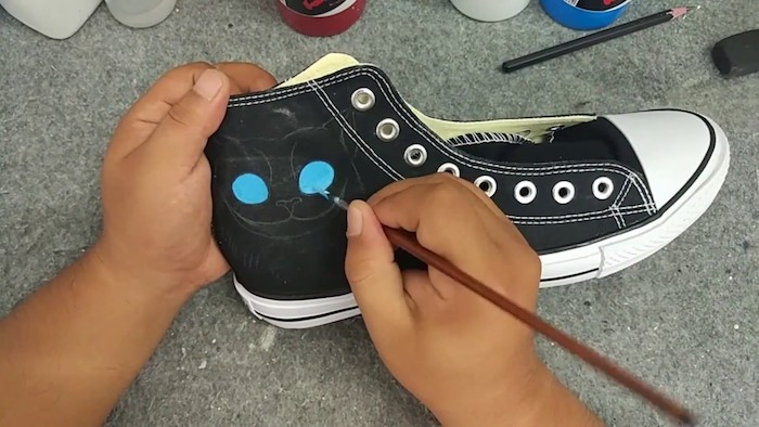 Le chat de cheshire dessin grands yeux bleus sur basket noir, idée comment personnaliser ses baskets noires, peinture pour chaussure