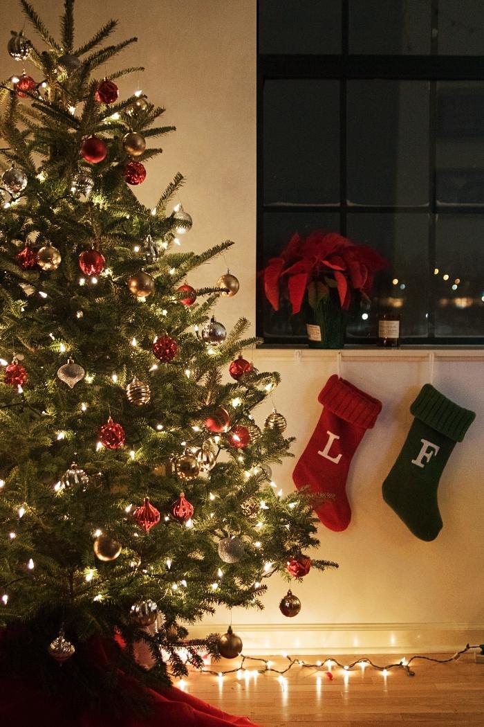 image de joyeux noel, fond d'écran noel avec un gros sapin naturel décoré d'ornements en rouge et or dans un salon cozy