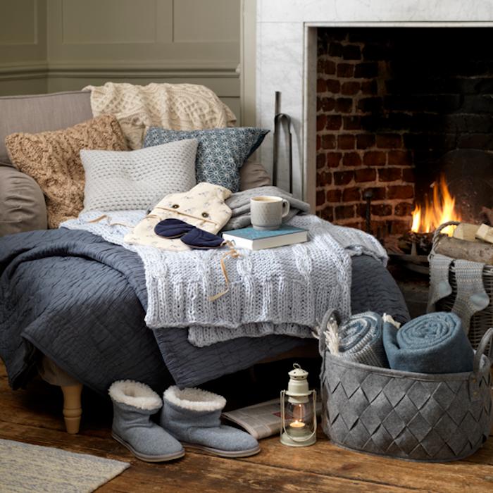 Cheminée avec feu, fauteuil double avec coussins tasse à café et livre, couleur taupe clair, décoration chambre grise