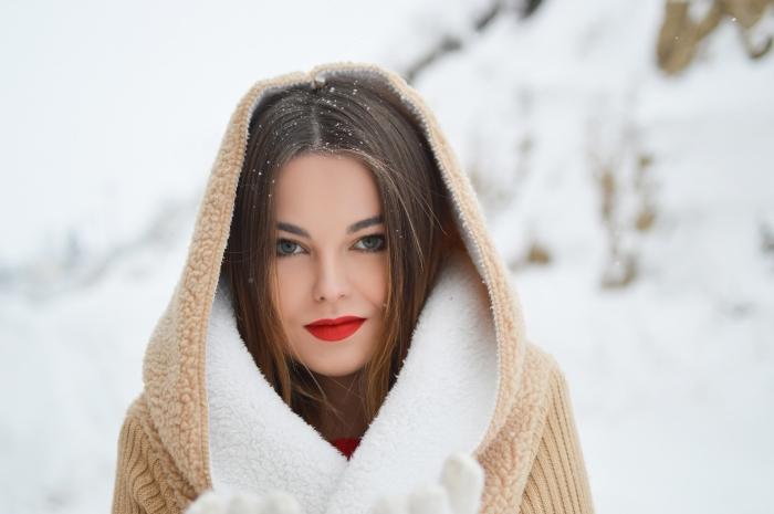 maquillage simple de Noël avec rouge à lèvre mat, look Noël femme habillée en pull rouge avec manteau beige